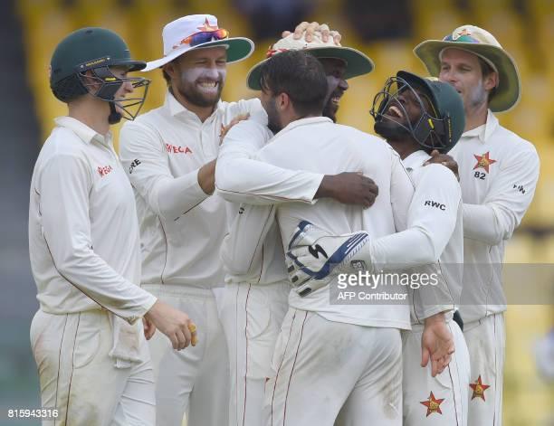 Zimbabwe cricketer Hamilton Masakadza celebrates with teammates after dismissing Sri Lankan cricket captain Dinesh Chandimal during the fourth day of...