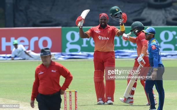 Zimbabwe cricketer Hamilton Masakadza raises his bat after scoring a century as teammate Tarisai Musakanda looks on during the third oneday...