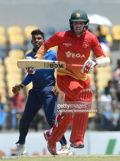Zimbabwe cricketer Malcolm Waller runs between the wickets as Sri Lankan cricketer Wanidu Hasaranga look on during the third oneday international...