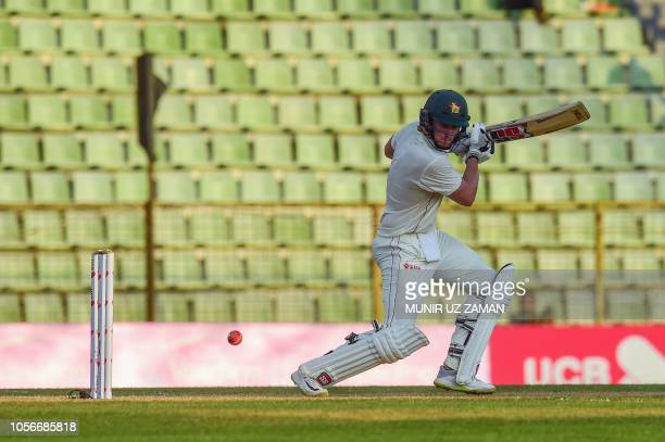 Zimbabwe cricketer Peter Moor plays a shot as the Bangladesh cricketer Nazmul Hossain Shanto looks on during the first day of the first Test cricket...