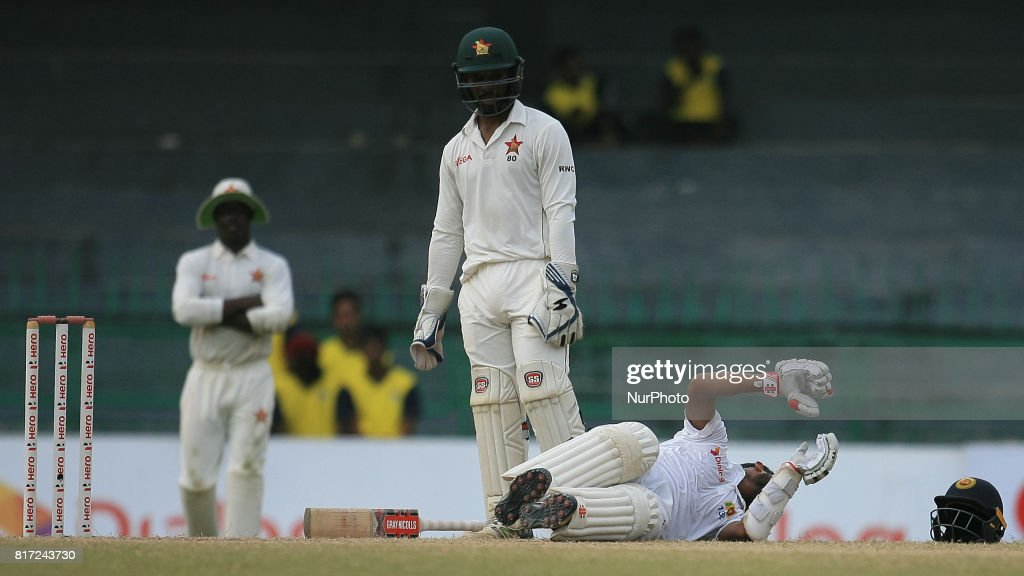 Zimbabwe cricketer Regis Chakabva(M) looks as Sri Lankan batsman Kusal Mendis(R) lies down due to a cramp in his leg during the 4th day's play in the only Test match between Sri Lanka and Zimbabwe at R Premadasa International Cricket Stadium in the capital city of Colombo, Sri Lanka on Monday 17th July 2017
