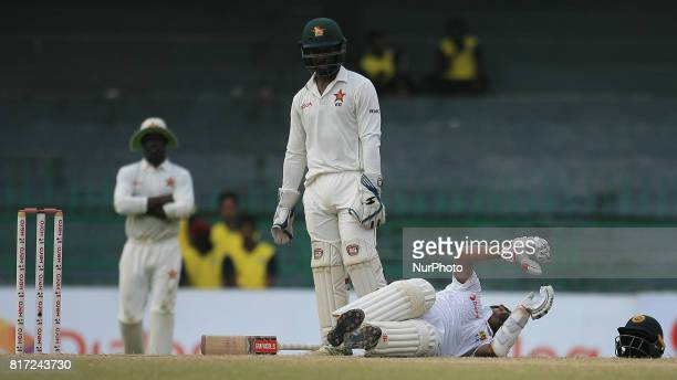 Zimbabwe cricketer Regis Chakabva looks as Sri Lankan batsman Kusal Mendis lies down due to a cramp in his leg during the 4th day's play in the only...