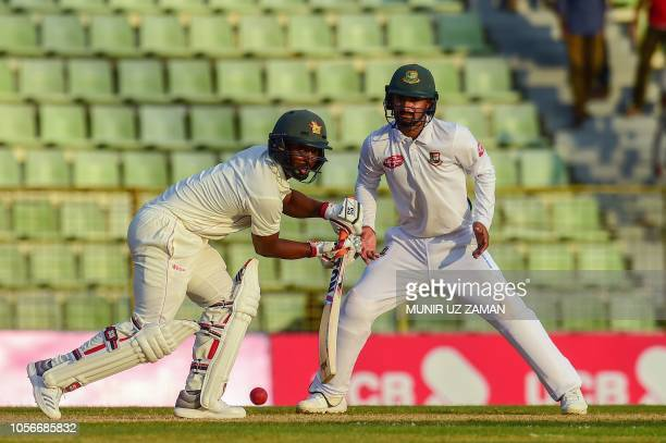 Zimbabwe cricketer Regis Chakabva plays a shot as the Bangladesh cricketer Nazmul Hossain Shanto looks on during the first day of the first Test...
