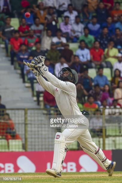 Zimbabwe cricketer Regis Chakabva takes a catch to dismiss Bangladesh cricketer Ariful Haque during the fourth day of the first Test cricket match...