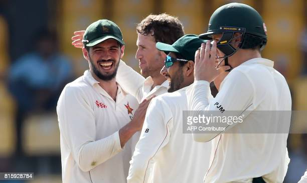 Zimbabwe cricketer Sean Williams and captain Graeme Cremer celebrate with teammates after dismissing Sri Lankan cricketer Dimuth Karunaratne during...