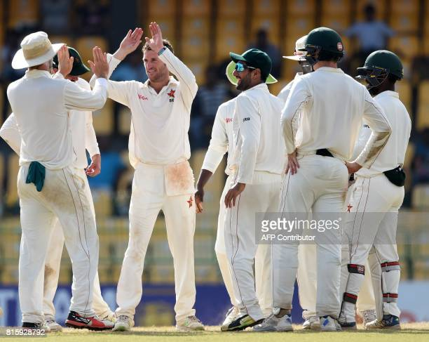 Zimbabwe cricketer Sean Williams celebrates with teammates after dismissing Sri Lankan cricketer Dimuth Karunaratne during the fourth day of a oneoff...