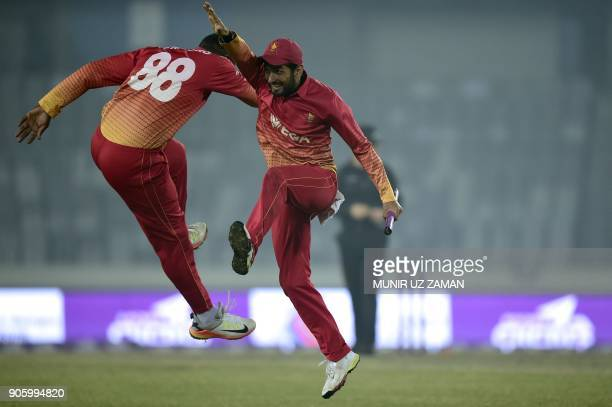 TOPSHOT Zimbabwe cricketer Sikandar Raza celebrates with his teammate after winning the second One Day International cricket match of the TriNations...