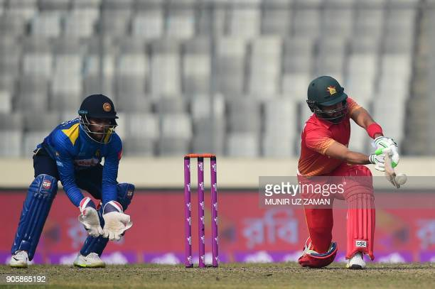 Zimbabwe cricketer Sikandar Raza plays a shot as Sri Lankan wicketkeeper Dinesh Chandimal looks on during the second One Day International cricket...