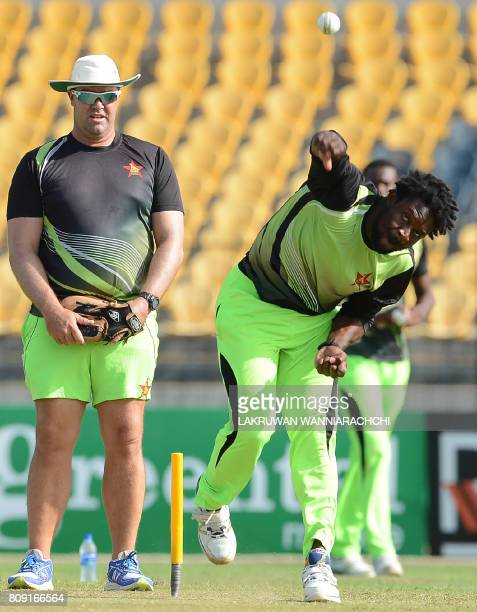 Zimbabwe cricketer Solomon Mire delivers a ball as coach Heath Streak looks on during a practice session at the Suriyawewa Mahinda Rajapakse...
