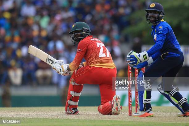 Zimbabwe cricketer Solomon Mire plays a shot as Sri Lanka's wicket keeper Niroshan Dickwella looks on during the 4th One Day International cricket...