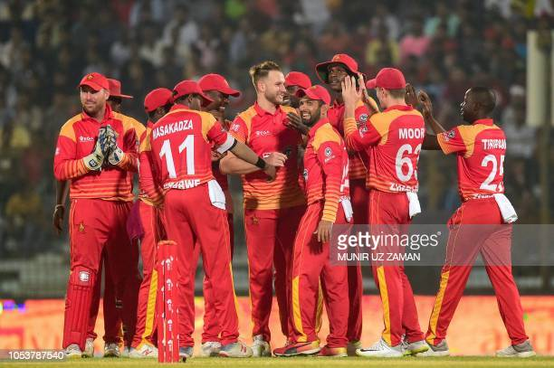 Zimbabwe cricketers celebrate after the dismissal of BangladeshI cricketer Liton Das during the third one day international cricket match between...