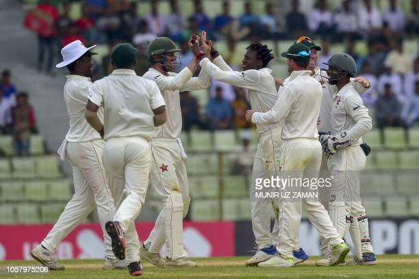 Zimbabwe cricketers celebrate after the dismissal of the Bangladesh cricketer Mehidy Hasan during the fourth day of the first Test cricket match...