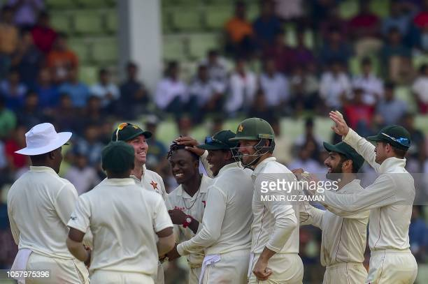 Zimbabwe cricketers congratulate teammate Brandon Mavuta after the dismissal of the Bangladesh cricketer Nazmul Islam during the fourth day of the...