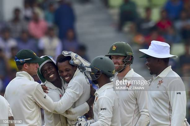 Zimbabwe cricketers congratulate teammate Wellington Masakadza after the dismissal of the Bangladesh cricketer Taijul Islam during the fourth day of...