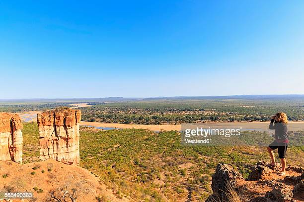 Zimbabwe, Masvingo, Gonarezhou National Park, woman looking at Runde River and Chilojo Cliffs