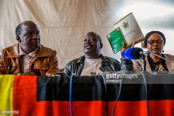 Zimbabwe National Liberation War Veterans Association Secretarygeneral Victor Matemadanda holds up the country's constitution at a press conference...
