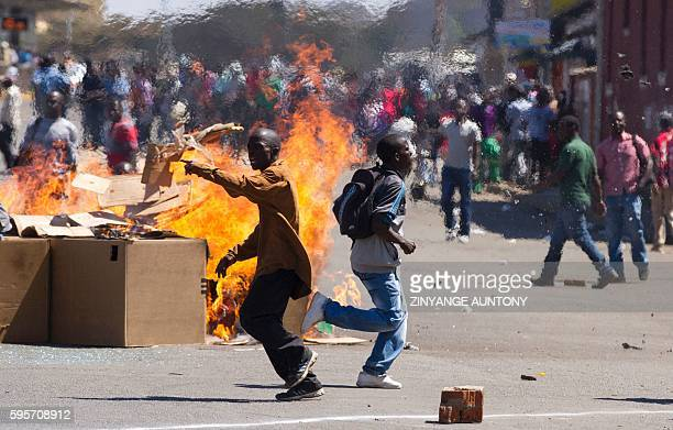Zimbabwe Opposition supporters set up a burning barricade as they clash with police during a protest march for electoral reforms on August 26 2016 in...