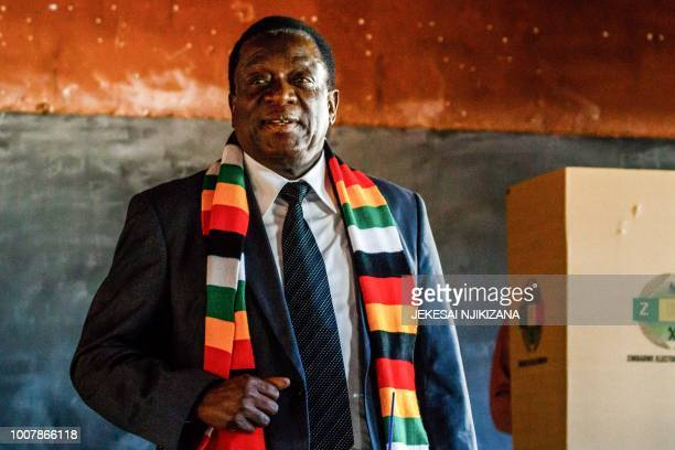 Zimbabwe President and candidate Emmerson Mnangagwa stands after casting his ballot at Sherwood Primary School in Kwekwe on July 30 2018, during...