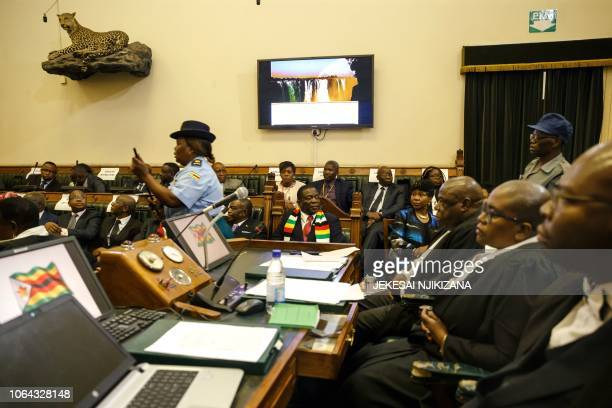 Zimbabwe President Emmerson Mnangagwa looks on as members of the Zimbabwe Republic Police enter to eject opposition party Members of Parliament who...
