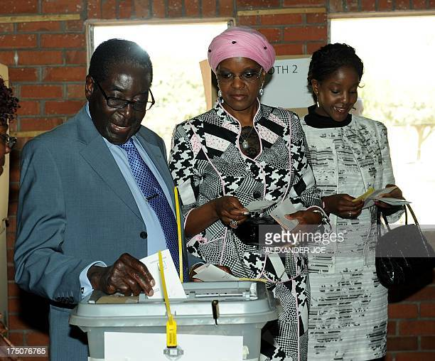 Zimbabwe President Robert Mugabe casts his vote by his wife Grace and daughter Bona at a polling booth in a school in Harare on July 31 2013...