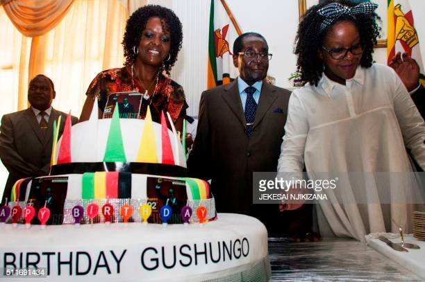 Zimbabwe President Robert Mugabe flanked by his wife Grace Mugabe and daughter Bona stand beside a cake adorned with the name of the Gushungo clan to...