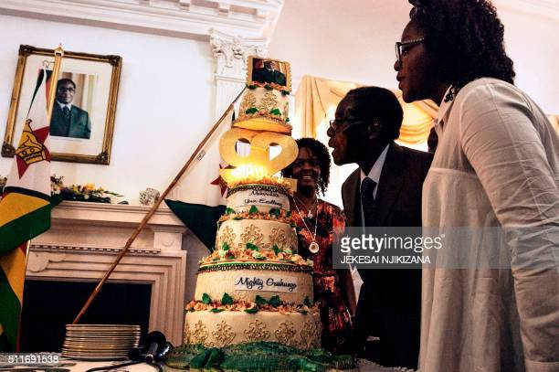 Zimbabwe President Robert Mugabe flanked by his wife Grace Mugabe and daughter Bona blows candles on his cake during a suprise party hosted by the...