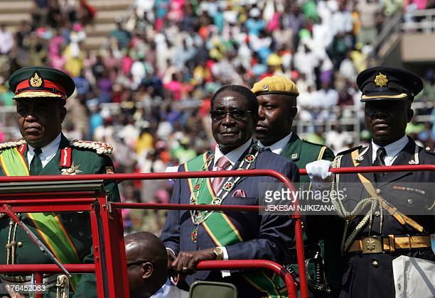Zimbabwe President Robert Mugabe flanked by Zimbabwe Defence Forces Commander Constantine Chiwenga inspects the guard of honor during the...