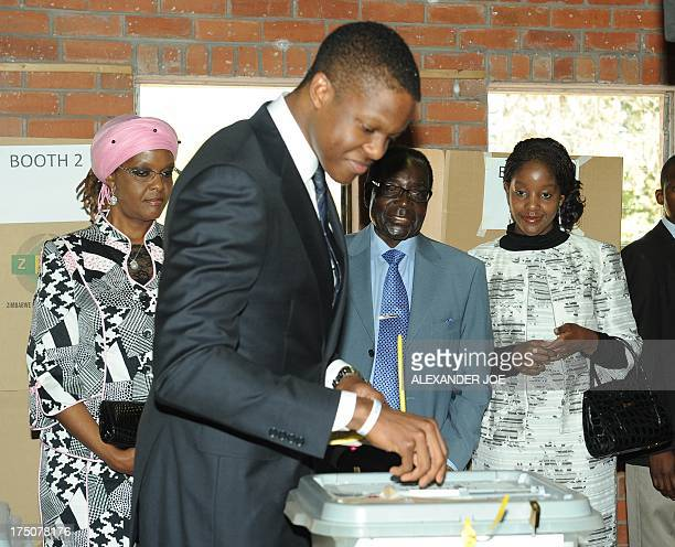Zimbabwe President Robert Mugabe watches with his wife Grace and daughter Bona as his son casts his vote at a polling booth in a school in Harare on...