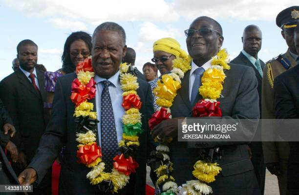 Zimbabwe President Robert Mugabe welcomes Zambian President Michael Sata upon his arrival in Harare on April 25 2012 for a twoday state visit...