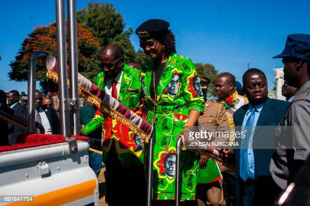 Zimbabwe President Robert Mugabe with his wife Grace Mugabe climbs the steps to a vehicle before meeting delegates during a Zimbabwe ruling party...