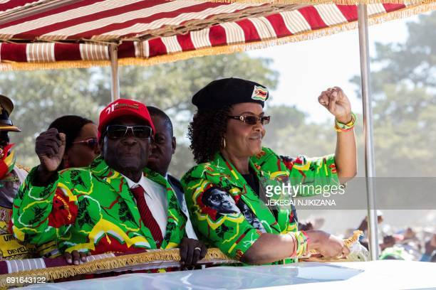 Zimbabwe President Robert Mugabe with his wife Grace Mugabe raise their fists in a vehicle before meeting delegates during a Zimbabwe ruling party...