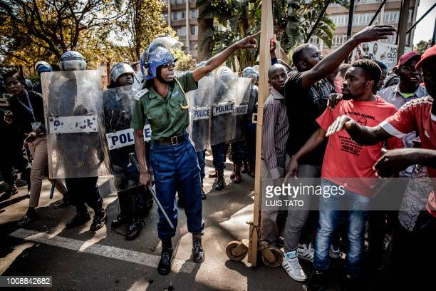 TOPSHOT Zimbabwean anti riot police officers close the entrance to the Rainbow Towers where the election's results were announced as supporters of...