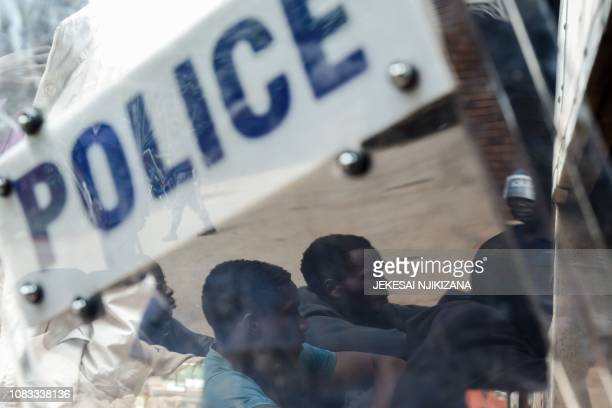 Zimbabwean antiriot police forces watch men arrested during violent protests triggered by a sudden rise in fuel prices announced by Zimbabwean...