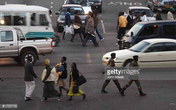 Zimbabwean army soldiers and pedestrians cross a street June 26 2008 in downtown Harare Zimbabwe President Robert Mugabe has come under widespread...