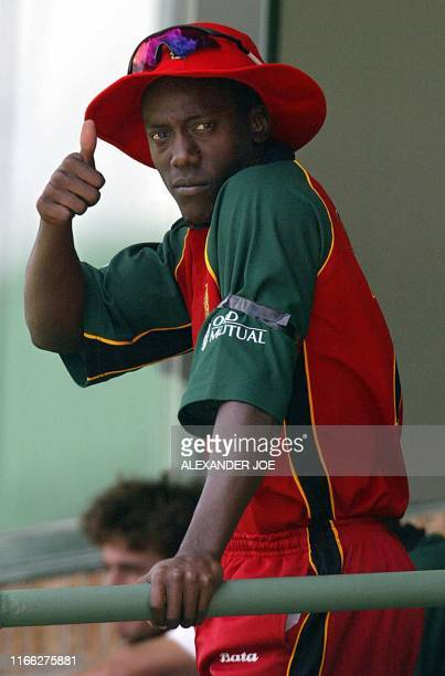 Zimbabwean batman Henry Olonga wears a black arm band as a sign of protest at the Harare Sports Ground 10 February 2003 a few moments before the...