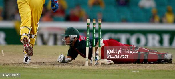 Zimbabwean batsman Heath Streak is sprawled on the ground after he has been stumped by Australian wicketkeeper Adam Gilchrist during their one-day...