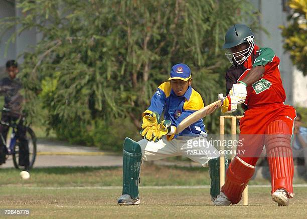 Zimbabwean batsman Stuart Matsikinyeri hits a ball as Bangladeshi wicket keeper Mushfiqur Rahim looks on during a practice match between Zimbabwe and...