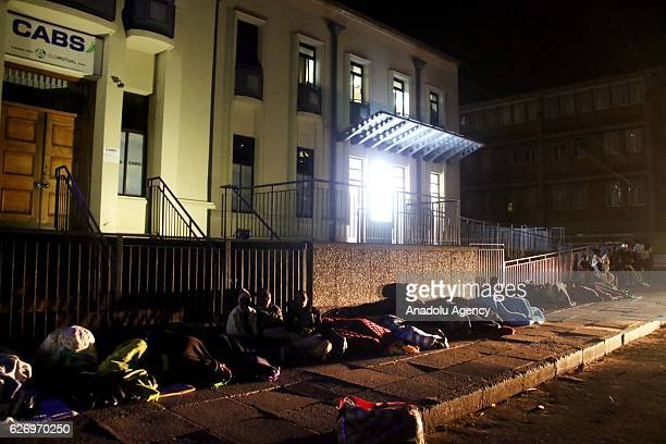 Zimbabwean citizens sleep at the pavement in front of a bank to withdraw their money at the night before the bank opens in the capital Harare...