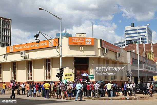 Zimbabwean citizens wait in front of a bank to withdraw their money at the night before the bank opens in the capital Harare Zimbabwe on December 01...