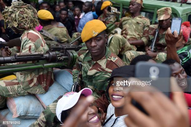 A Zimbabwean Defence Force soldier poses for selfiepictures with two women as they take part in a march in the streets of Harare on November 18 2017...