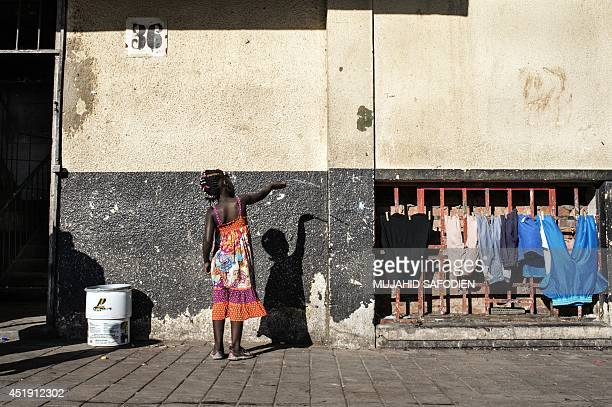 Zimbabwean girl draws on June 6 2014 with a stick on the wall of a building illegally occupied by mainly Zimbabwean immigrants in the central...
