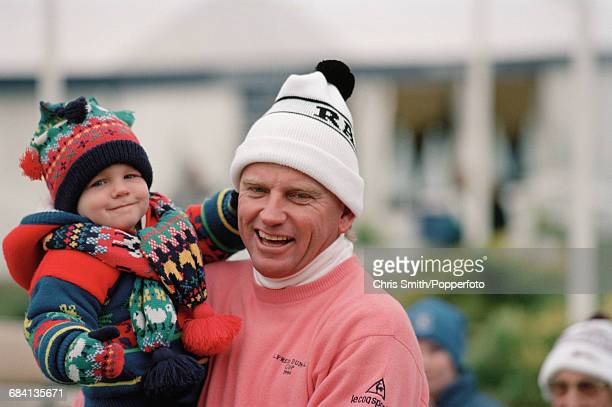 Zimbabwean golfer Nick Price pictured holding a young child during a break in competition for the Zimbabwe team in the 1994 Dunhill Cup golf...