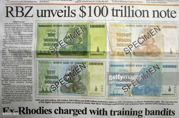 A Zimbabwean government daily newspaper unveils the new hundred trillion dollar note on January 16 2009 as the country battles with inflation which...