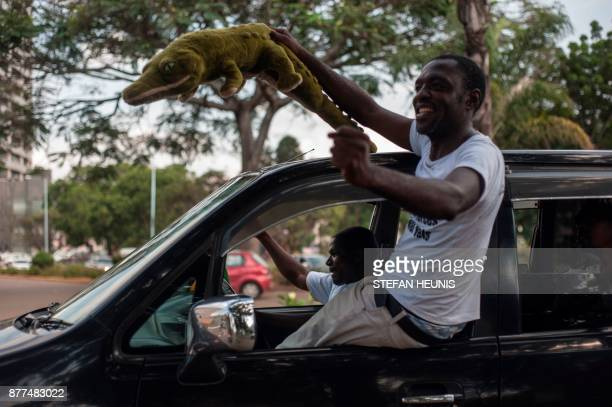 A Zimbabwean holds a crocodile soft toy as he celebrates from a car the arrival of Zimbabwe's ousted vice president Emmerson Mnangagwa at the...