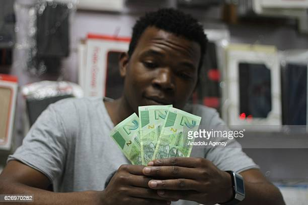 Zimbabwean holds newly issued banknotes in Harare Zimbabwe on December 01 2016 Zimbabwe faces the worst financial crisis on cash shortage within last...
