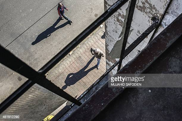 Zimbabwean immigrants walk on June 6 2014 in front of the main entrance of a building illegally occupied by mainly Zimbabwean immigrants in the...