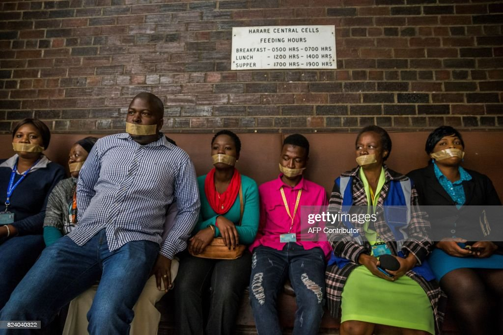 TOPSHOT - Zimbabwean journalists sit with their mouths tapped after marching to Harare Central Police Station during a protest against police methods on July 28, 2017 in Harare. / AFP PHOTO / Jekesai NJIKIZANA