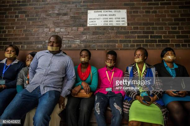 TOPSHOT Zimbabwean journalists sit with their mouths tapped after marching to Harare Central Police Station during a protest against police methods...