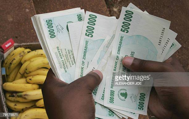 A Zimbabwean man counts a big stack of money to buy some bananas in Harare 23 January 2008 as the ongoing economical crisis in Zimbabwe leads to the...