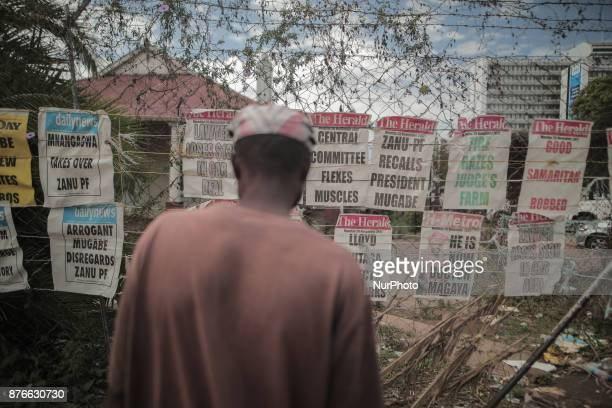 A Zimbabwean man reads newspapers hanging on a street in the capital Harare Zimbawe on 20 November 2017 Newspapers are held down by rocks to stop...